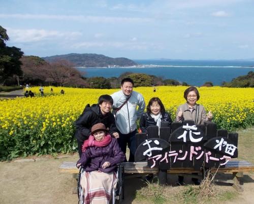 菜の花と海をバックに記念撮影